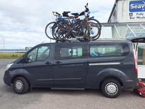 Bikes loaded onto John o'Groats Bike Transport Company minibus